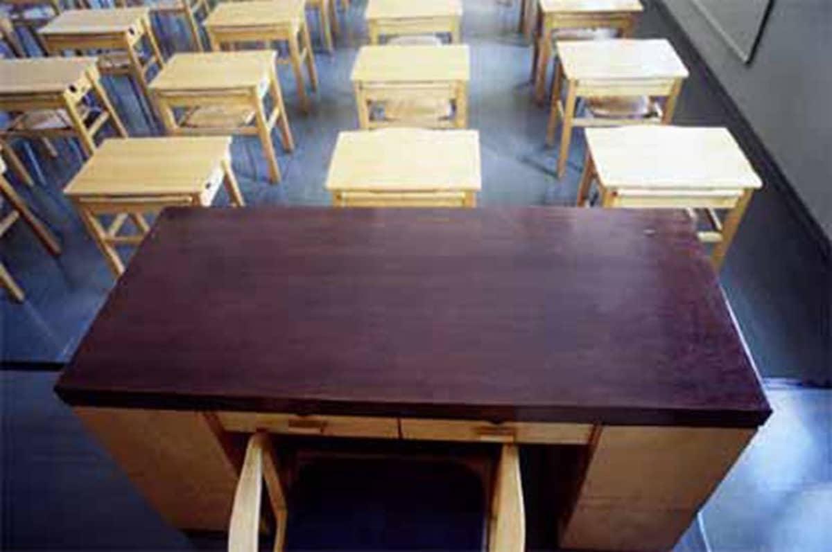 Tyhjät opettajanpöytä ja pulpettirivi