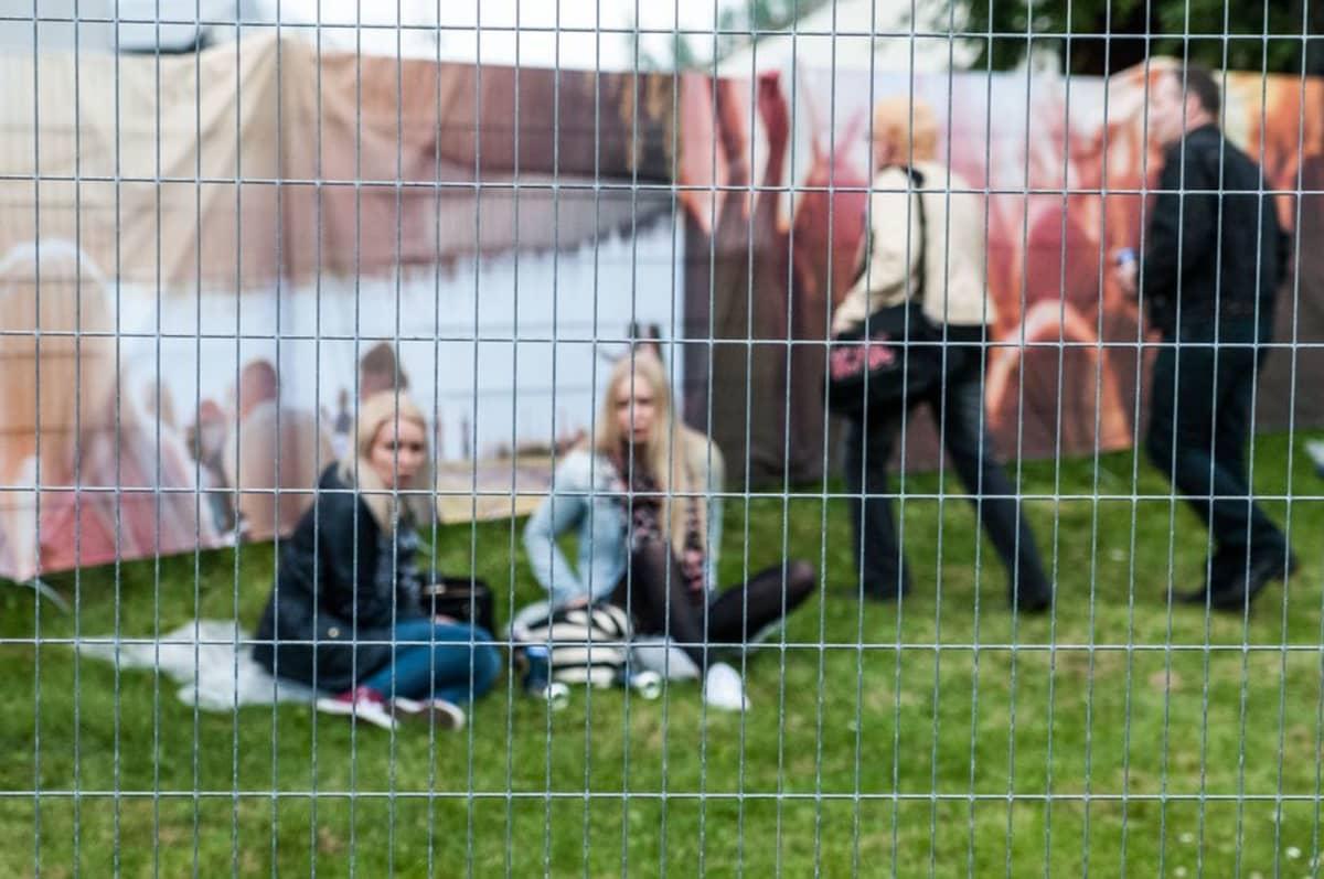 Ihmisiä anniskelualueen aidan takana festivaalilla