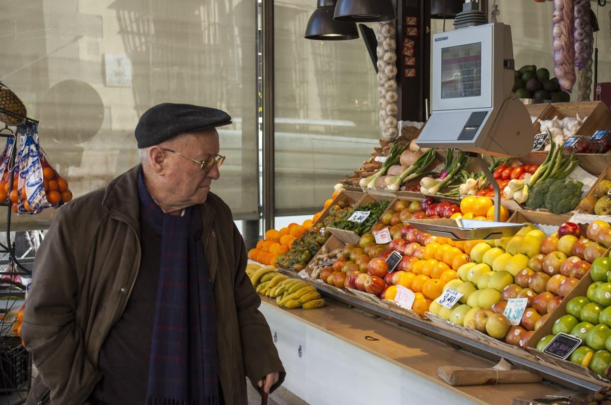 Mies katselee hedelmiä myyntikojussa. Espanjassa on päästy eroon pahimmasta talouskriisistä.
