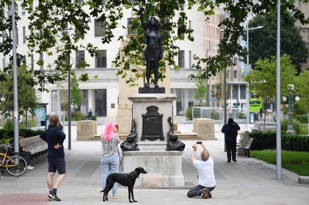 ihmisiä valokuvaamassa Jen Reidiä esittävää patsasta.