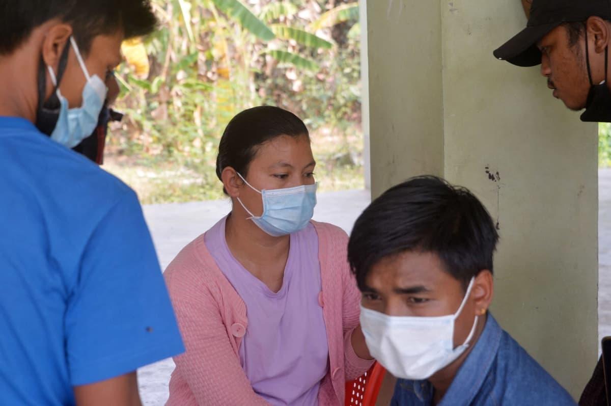 Myanmarin protesteissa kuolleen naisen perhe odottaa ruumiin luovuttamista sairaalan ulkopuolella.