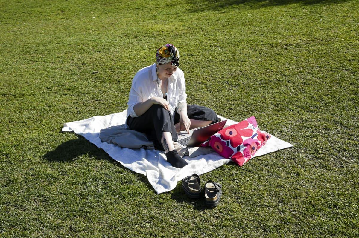 ainen opiskelee etänä puistossa.