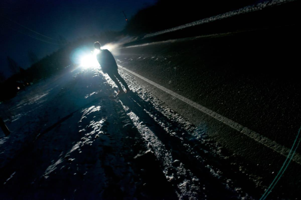 Ihminen seisoo pimeässä yössä auton valoissa tien varressa talvella.