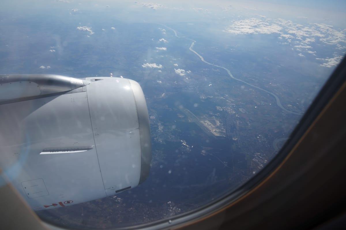 Kuva lentokoneen ikkunasta ulos; alhaalla häämöttää maisema ja asutusta.
