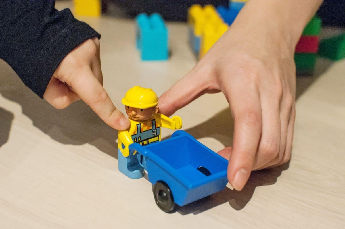Lapsi ja aikuinen leikkivät leluilla.