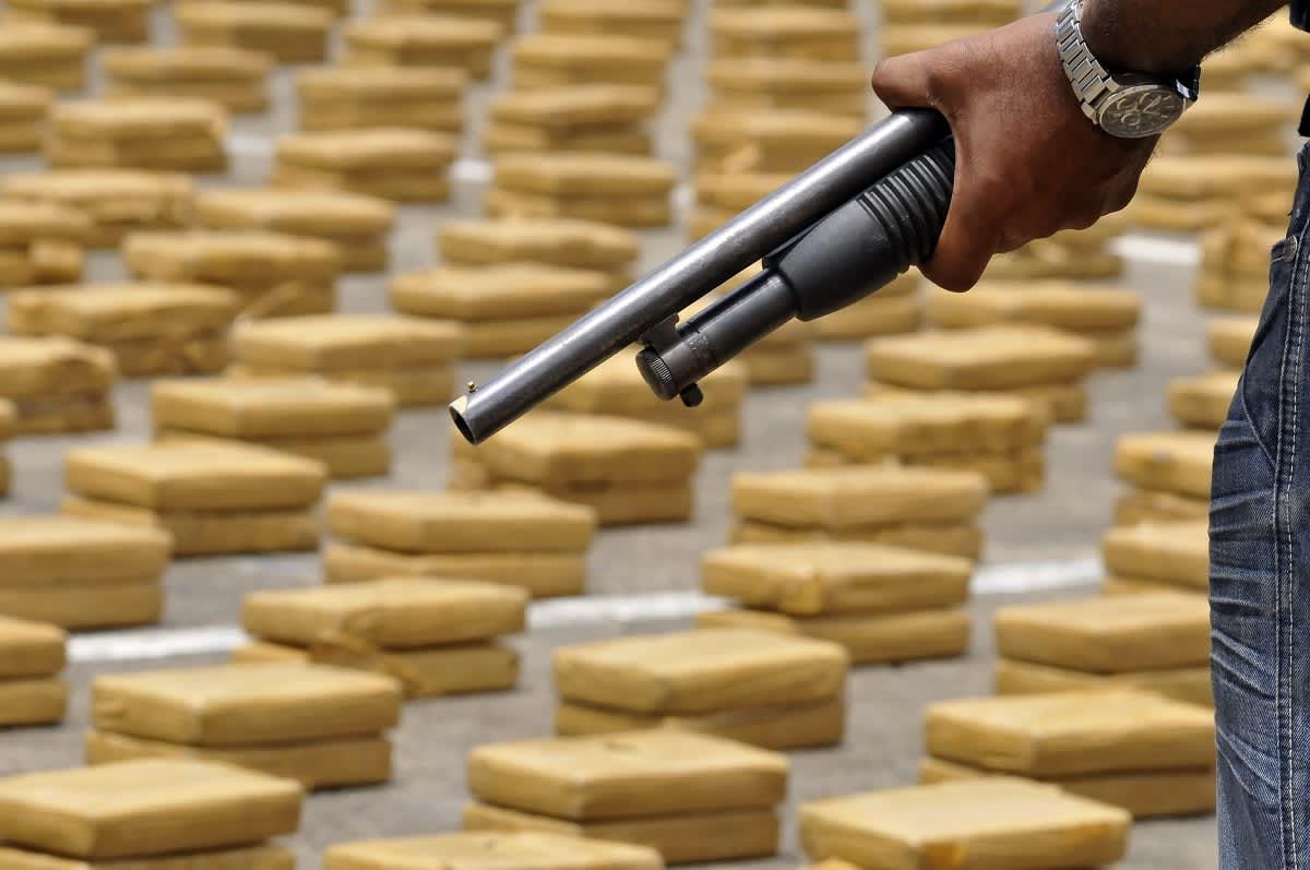 Ase  miehen kädessä taustalla kymmenittäin keltaisia paketteja maassa.
