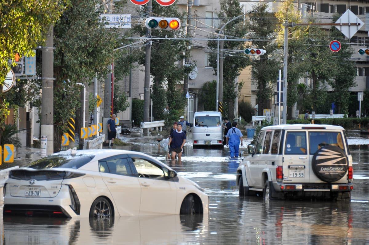 Ihmisiä kävelemässä tulvivassa Kawasakin kaupungissa lähellä Tokiota 13. lokakuuta.