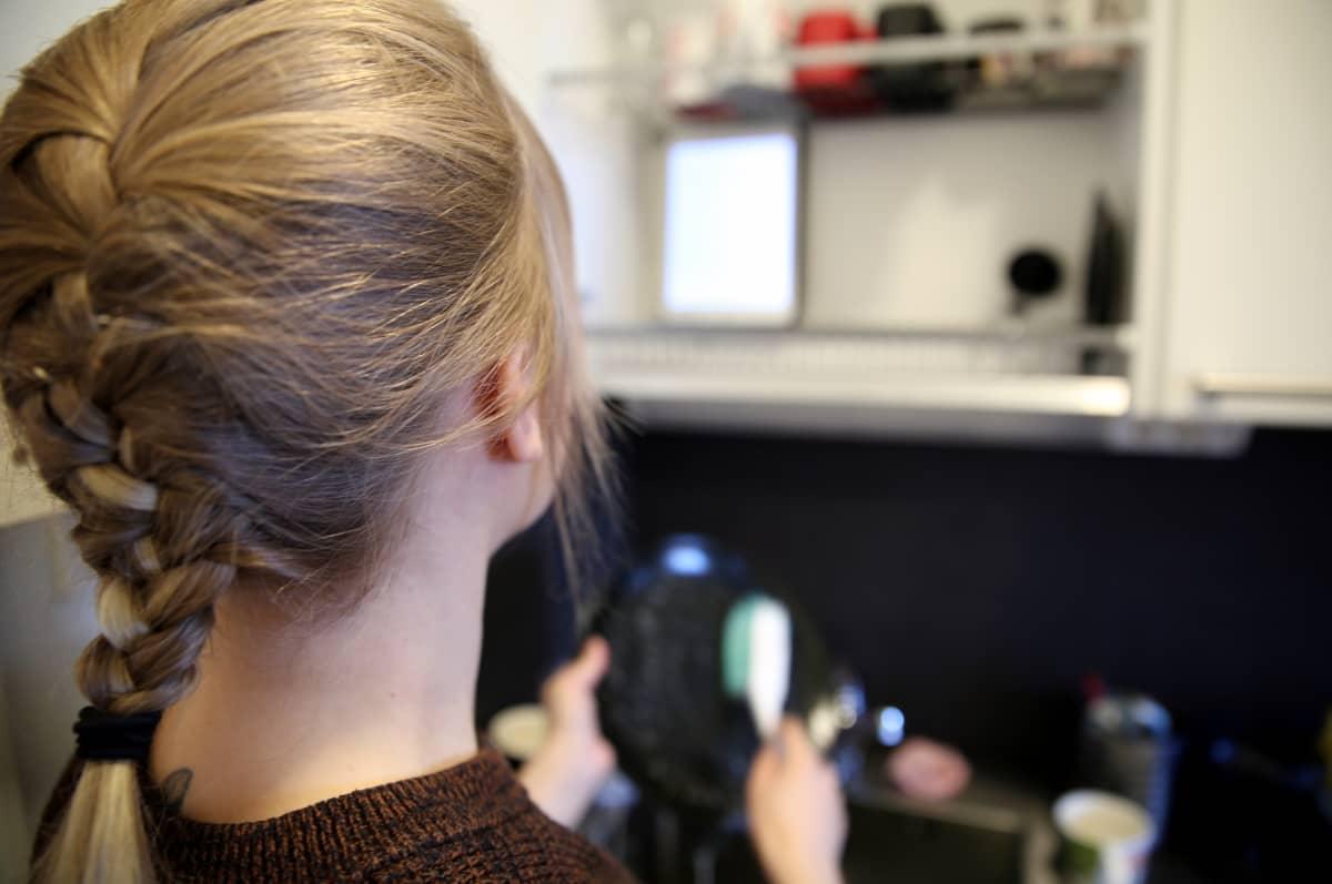 Ponihäntäinen nuori nainen tiskaa etualalla ja mobiililaite on asetettu eteen tiskikaappiin. Näytöltä nainen lukee kirjaa.