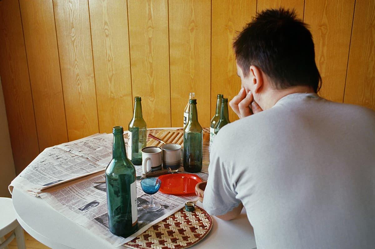Mies istuu pöydässä, joka on täynnä tyhjiä pulloja.