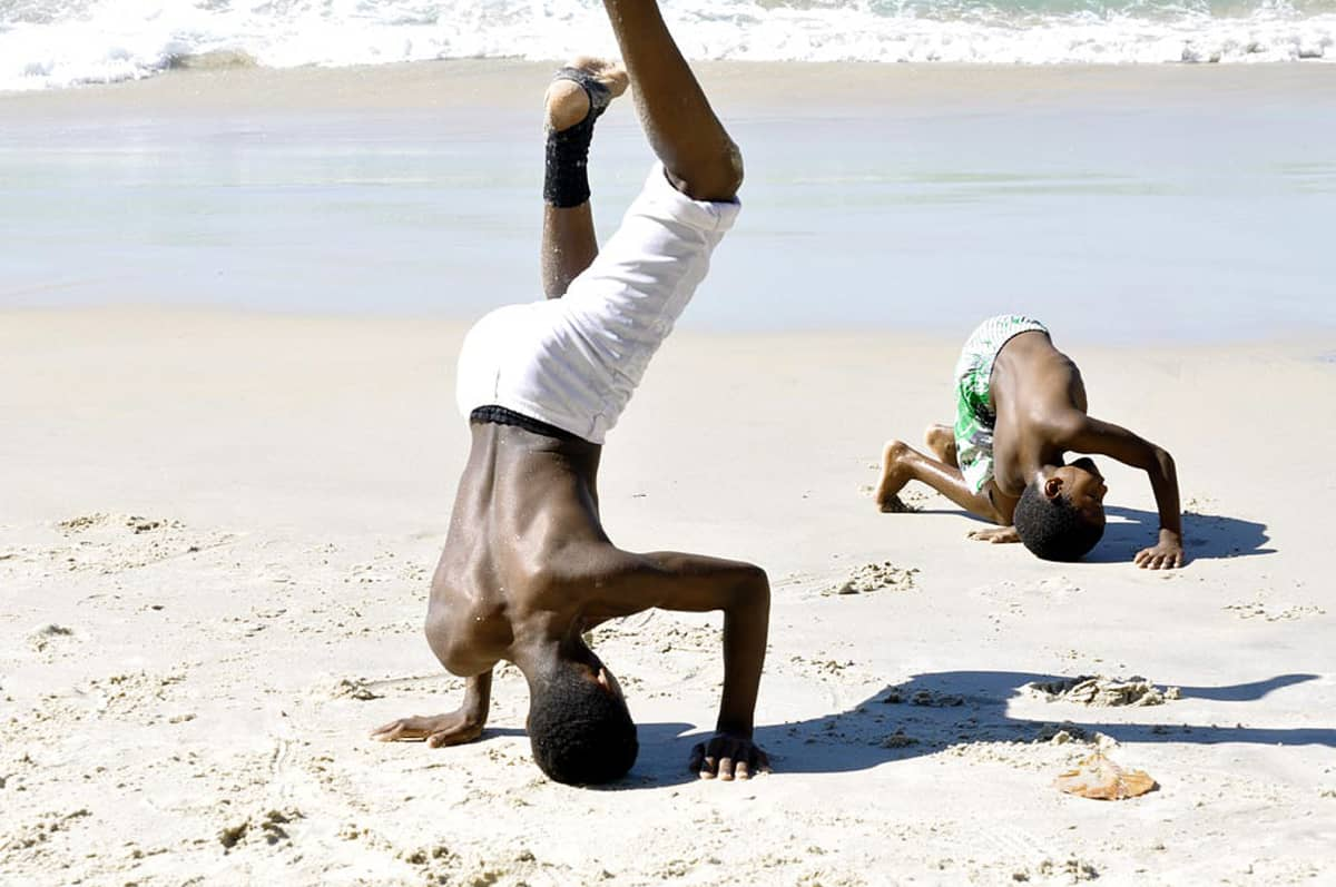 Pojat harjoittelevat capoeiraa rannalla.