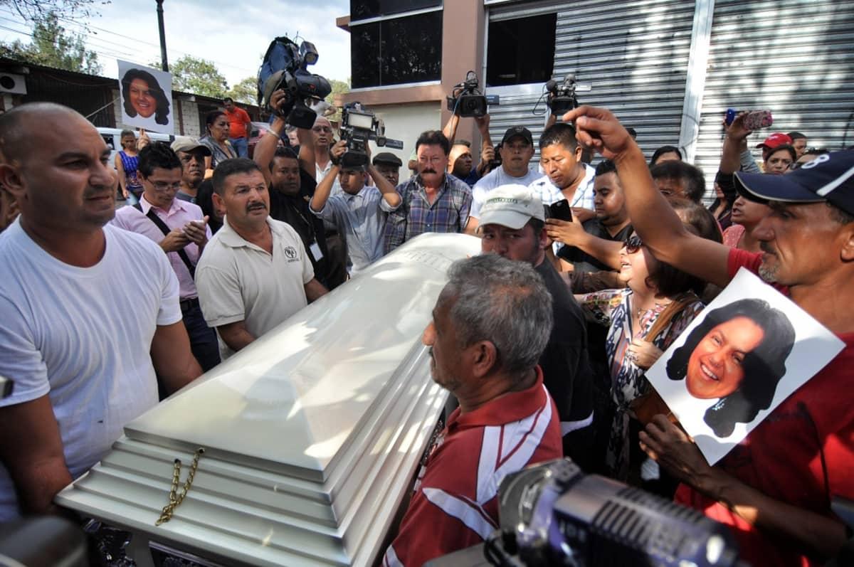 Joukko miehiä kantaa valkoista arkkua väentungoksessa. Vieressä on mies, jolla on kädessään Cáceresin kuva. Ympärillä on lukuisia kameramiehiä, jotka kurkottelevat ja nostelevat kameroitaan korkealle saadakseen kuvia hautajaissaatosta.