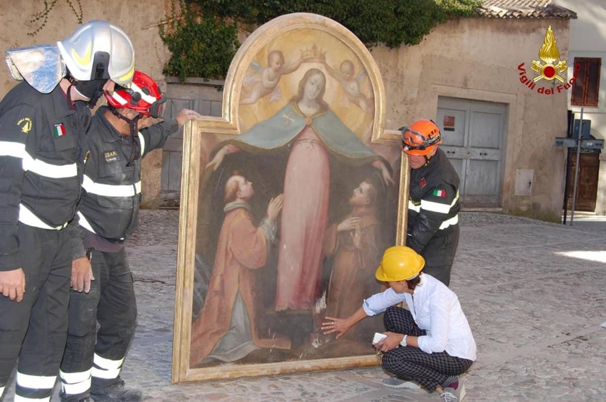 Kolme palomiestä pitelee pystyssä naispyhimystä esittävää maalausta, jonka tuhoja tutkii kyykyllään oleva nainen.