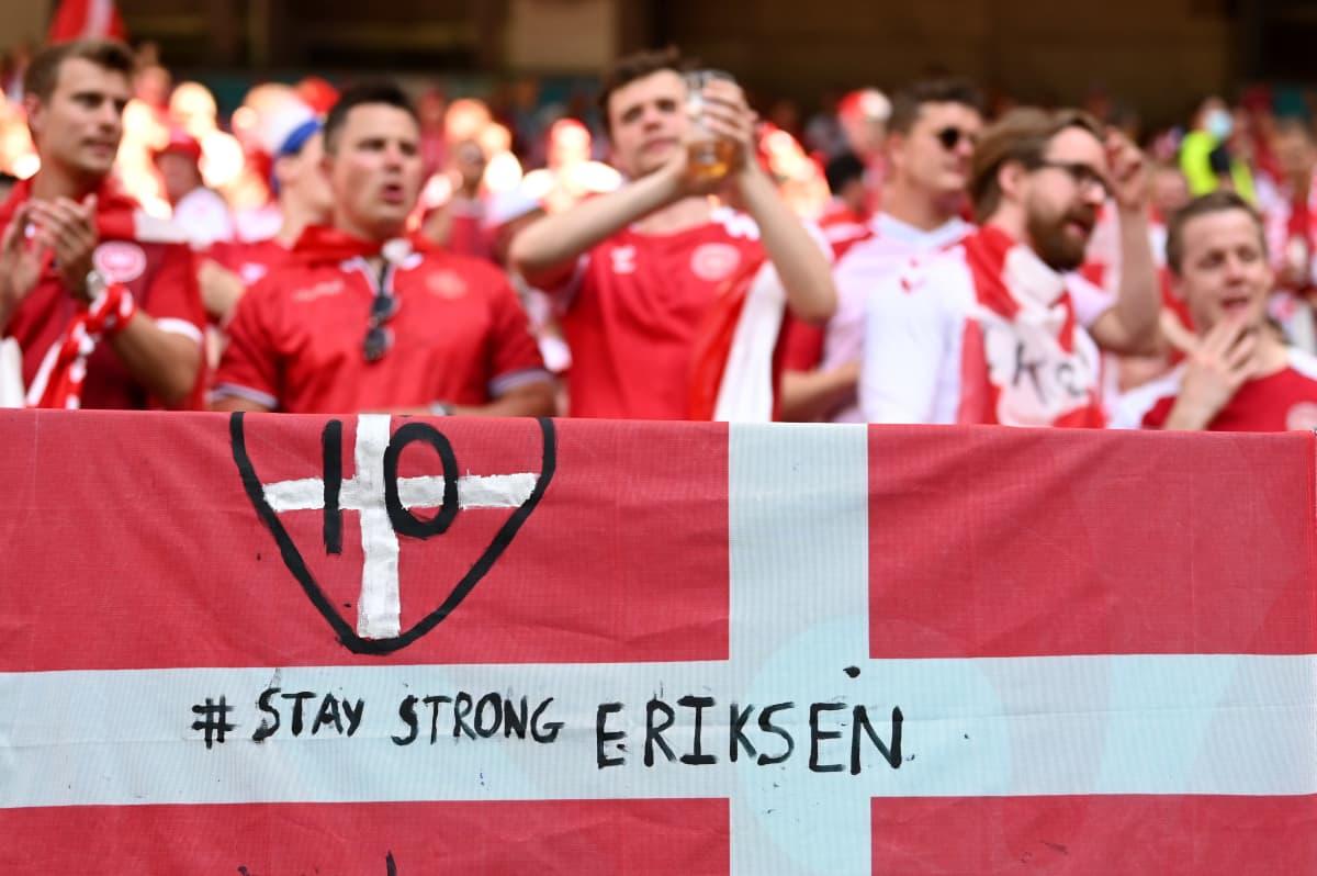 """Tanskalaisfanit osoittamassa tukeaan Christian Eriksenille Kööpenhaminan Parken-stadionin katsomossa. Etualalla olevassa Tanskan lipussa lukee """"Pysy vahvana Eriksen""""."""