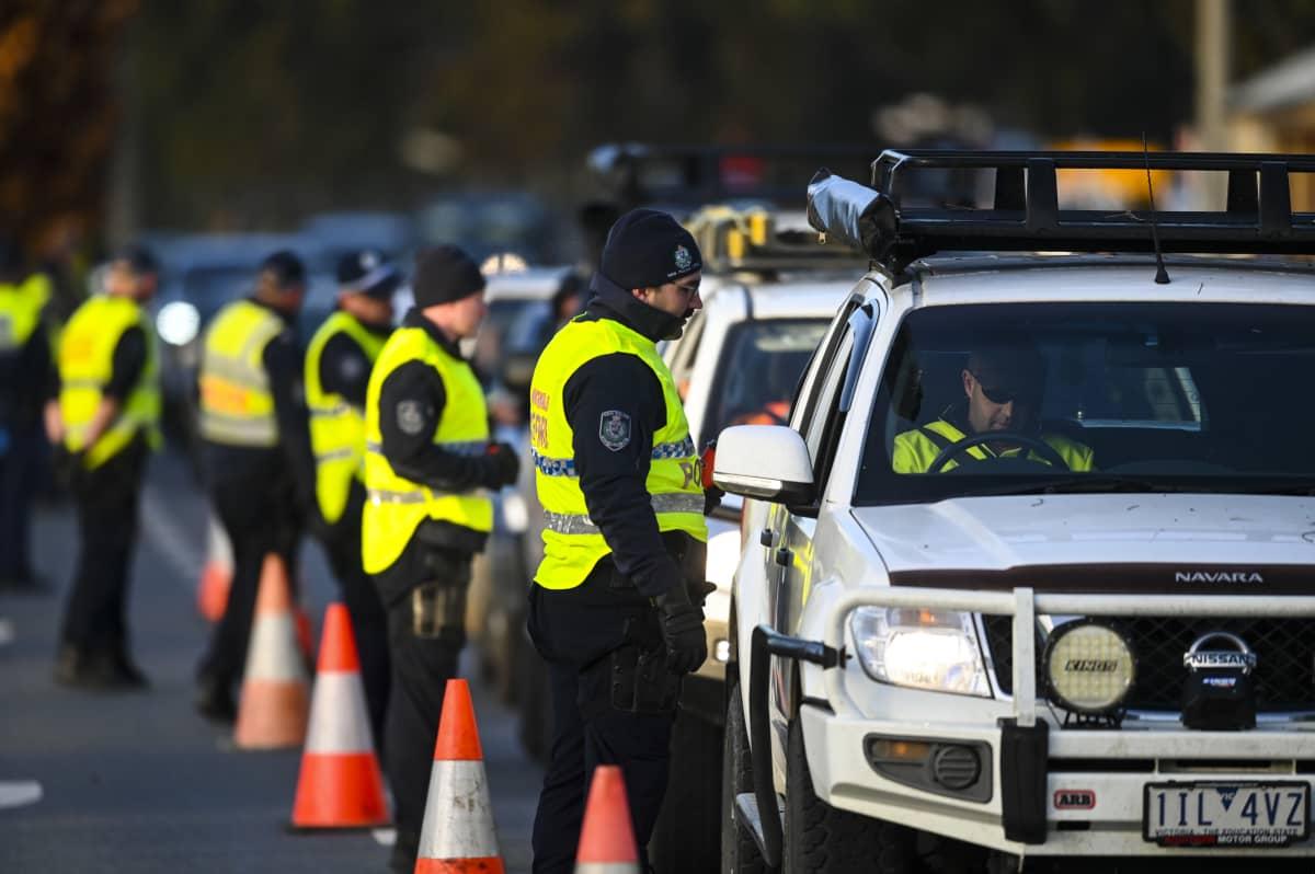 Pitkä rivi poliiseja autojonon vieressä