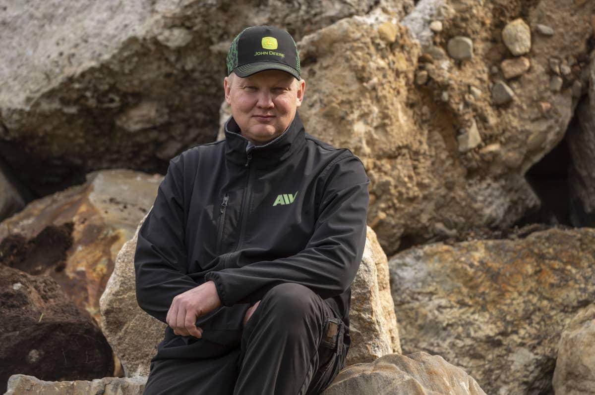 Tuomo Latvalan istuu kivikasan vieressä tilallaan.