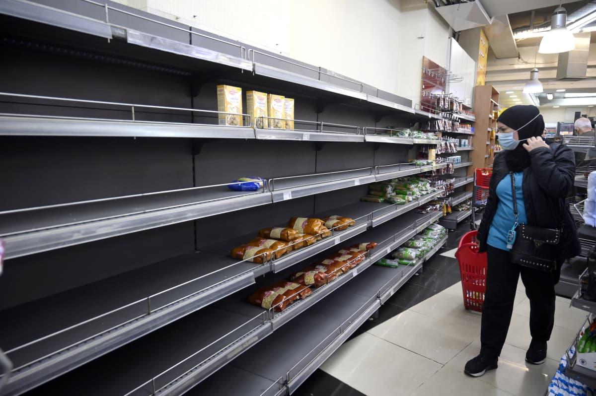 Nainen ostamassa elintarvikkeita Beirutilaisessa elintarvikekaupassa.   A customer walks past an almost empty shelf in a supermarket in Beirut, Lebanon, 24 March 2021.