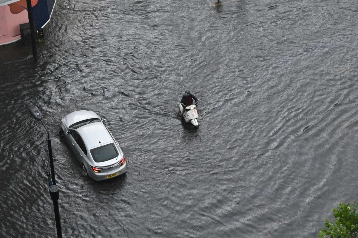 Auto ja moottoripyörä keskellä tulvivaa katua.