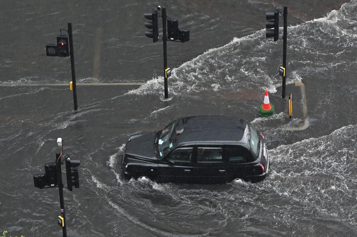 Lontoolainen taksi ajaa tulvivalla kadulla.