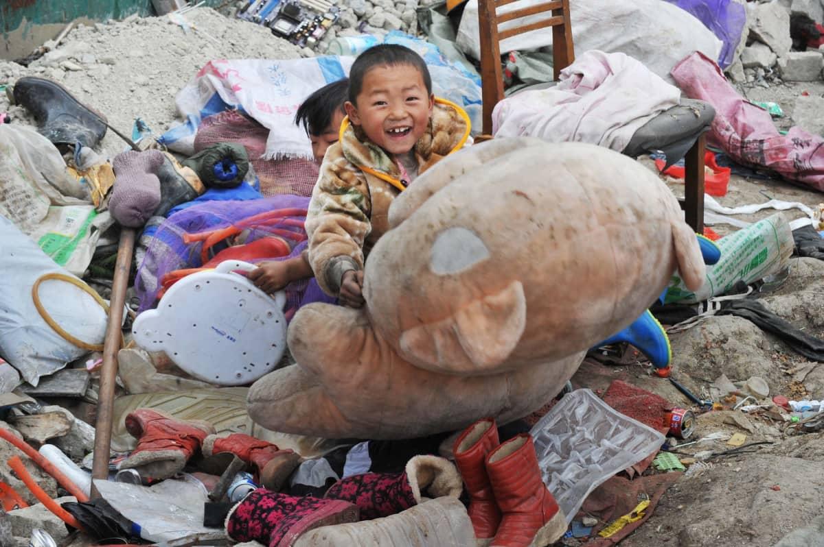Lapsi hymyilee onnellisena löydettyään ison nallen kaatopaikalta Guiyangin kaupungissa Guizhoun provinssissa vuonna 2015.