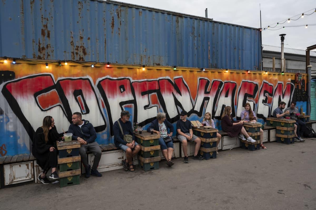 Ihmisiä istumassa pöytien ääressä suuren Kööpenhamina-graffitin edessä.