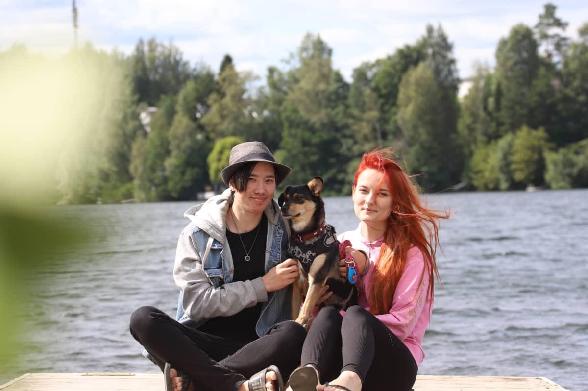 Akira Greus ja Linda Marin istuvat laiturilla Pepi-koira sylissään