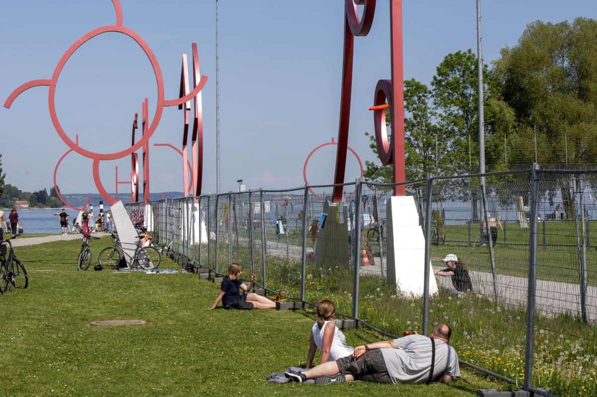 Punaisista, muutaman metrin päässä toisistaan seisovista veistoksista koostuva taideteos. Teoksen läpi kulkee tilapäinen raja-aita, jonka molemmin puolin ihmisiä.