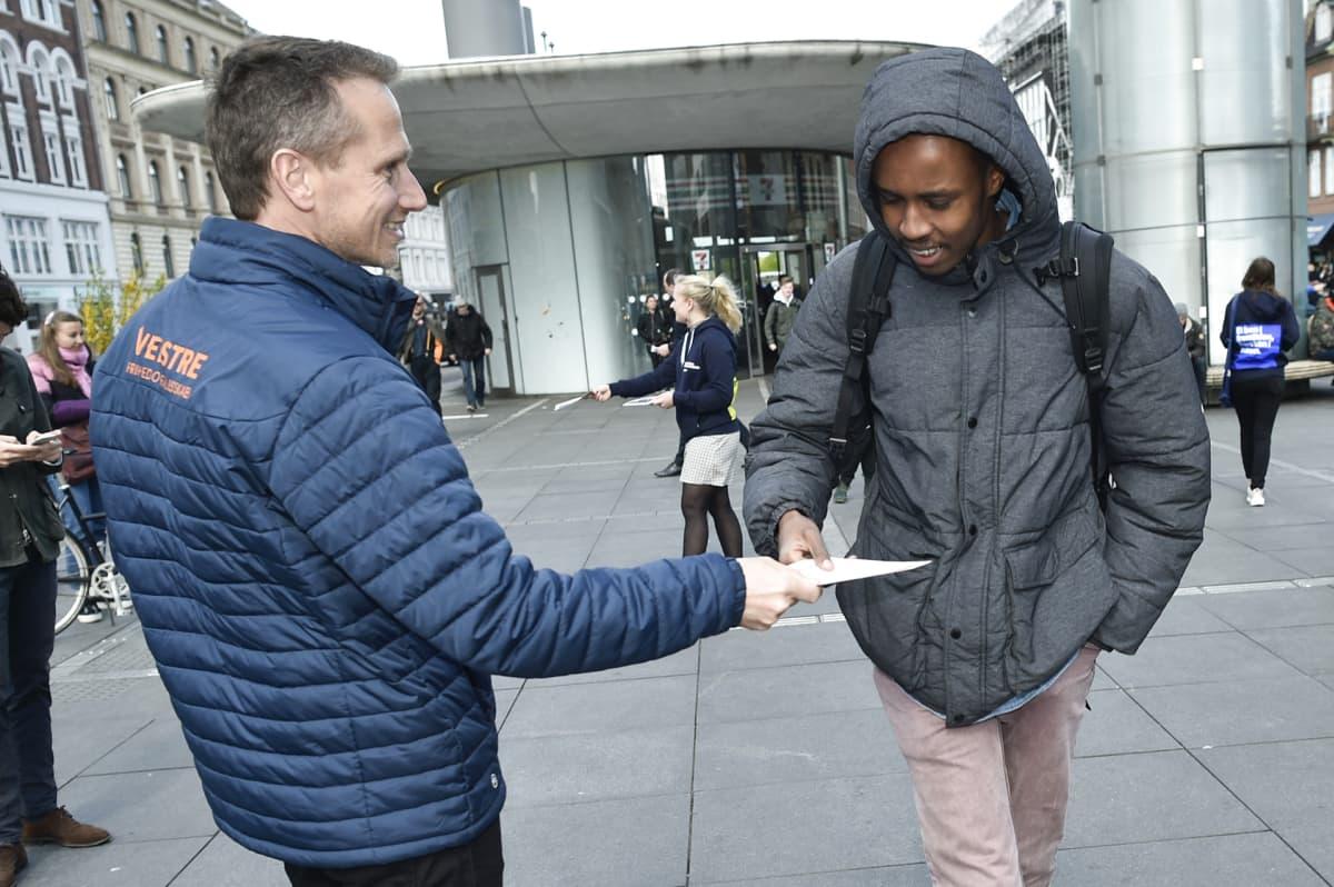 Kristian Jensen ojentaa vaalimainosta maahanmuuttajalle.
