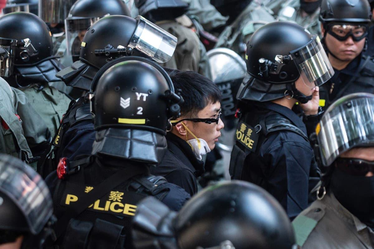 Poliisit saattoivat miestä ulos mielenosoituksesta Hongkongissa 2. marraskuuta.