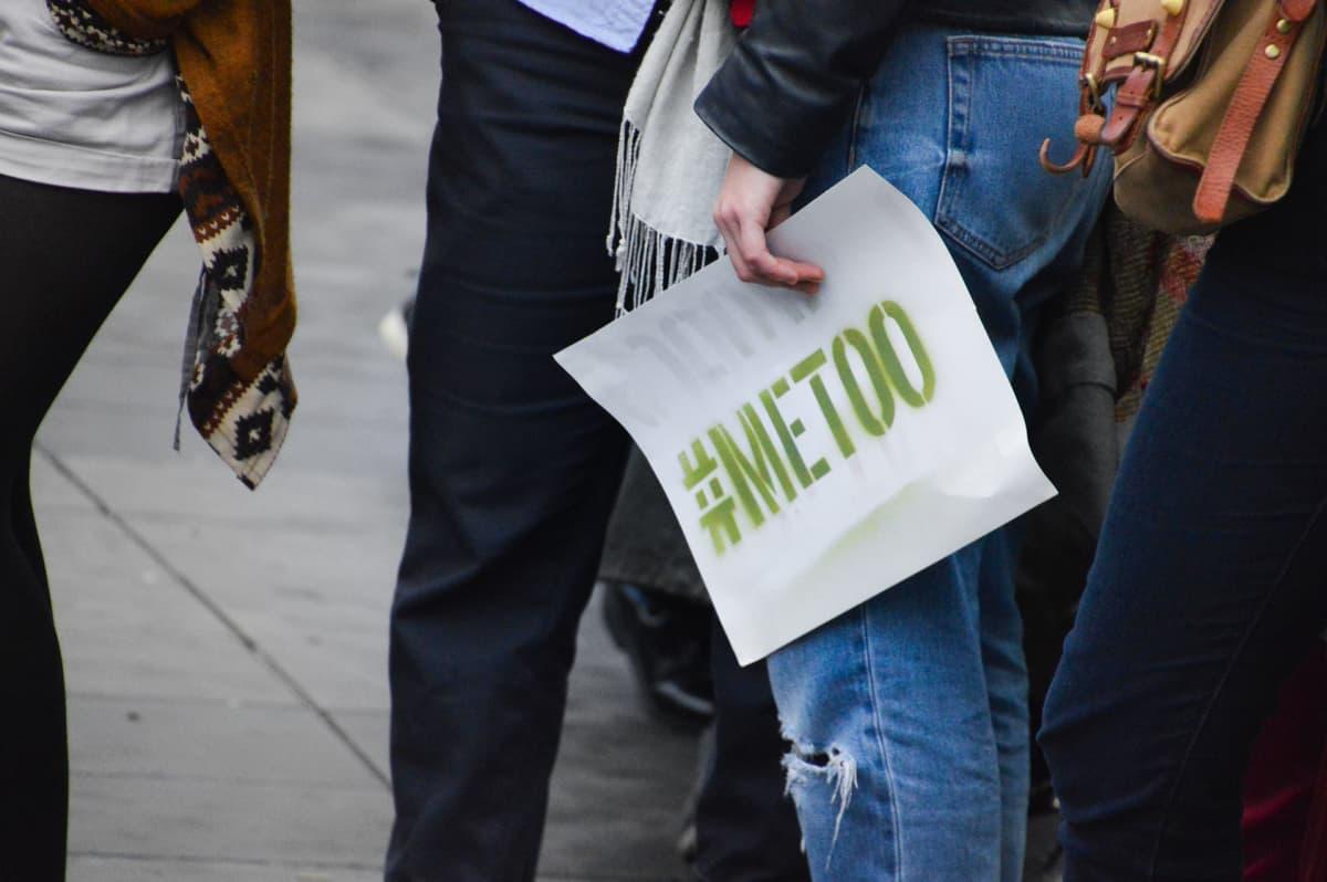 Naisen kädessä kyltti jossa lukee #MeToo