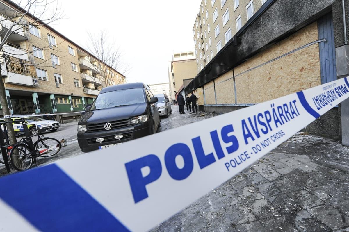 Poliisin eristysnauha kadulla, taustalla auto.