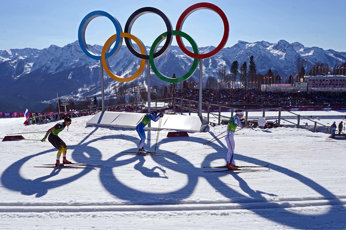Naiset hiihtävät olympiarenkaiden ohi.