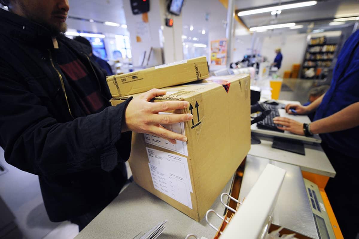 Mies hakee pakettia postista.