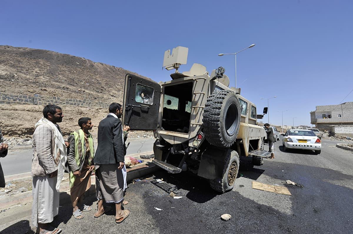 Jemeniläiset katselevat armeijan miehistönkuljetusajoneuvoa, joka on tuhoutunut