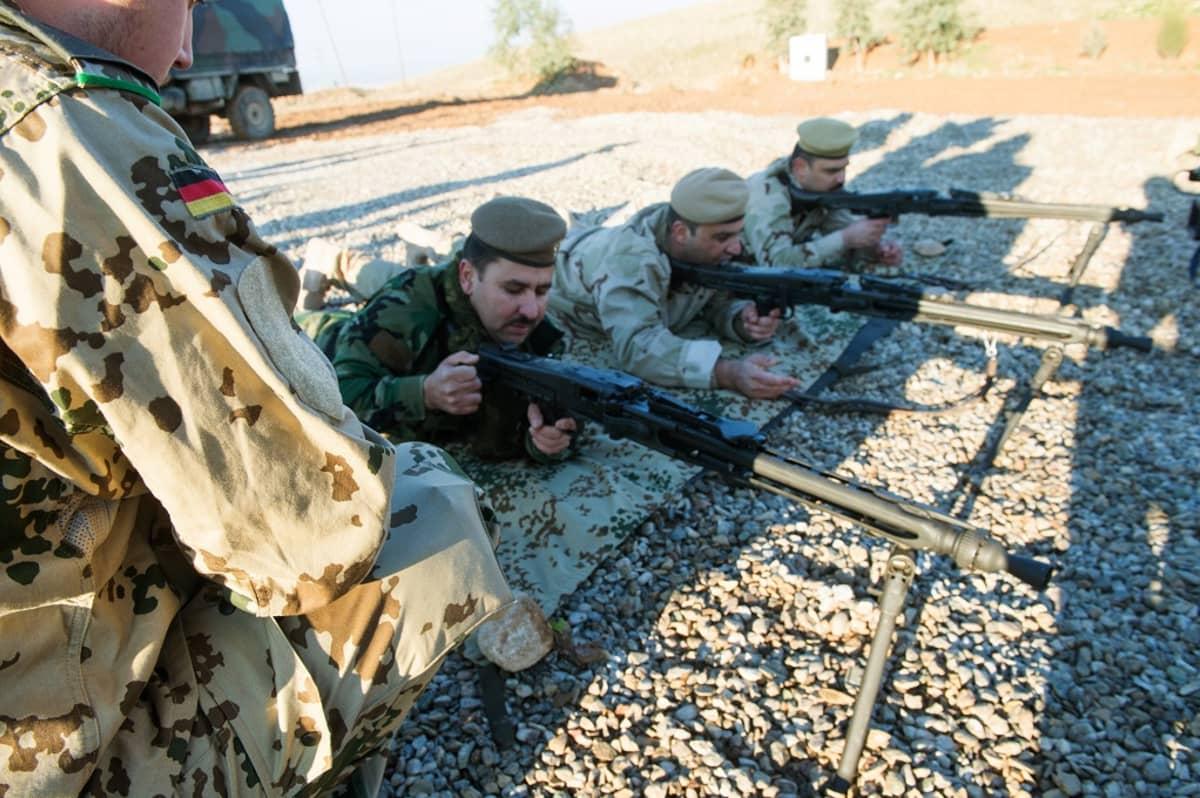 kurdisotilaita makuulla konekiväärien kanssa
