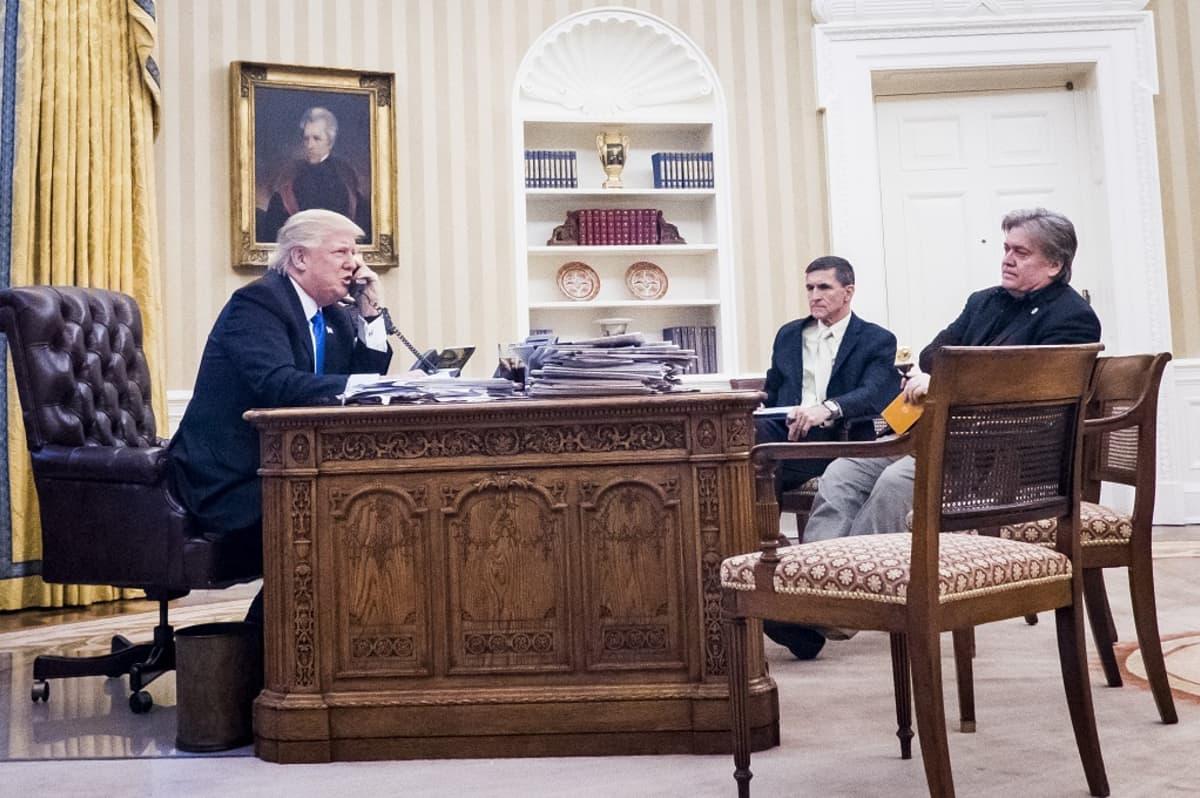 Yhdysvaltain presidentti Donald Trump hoitamassa dipolomaattisia suhteita puhelimitse. Huoneessa ovat myös kansallisen turvallisuuden neuvonantaja Michael Flynn (keskellä) ja presidentin pääneuvonantaja Steve Bannon (oikealla).