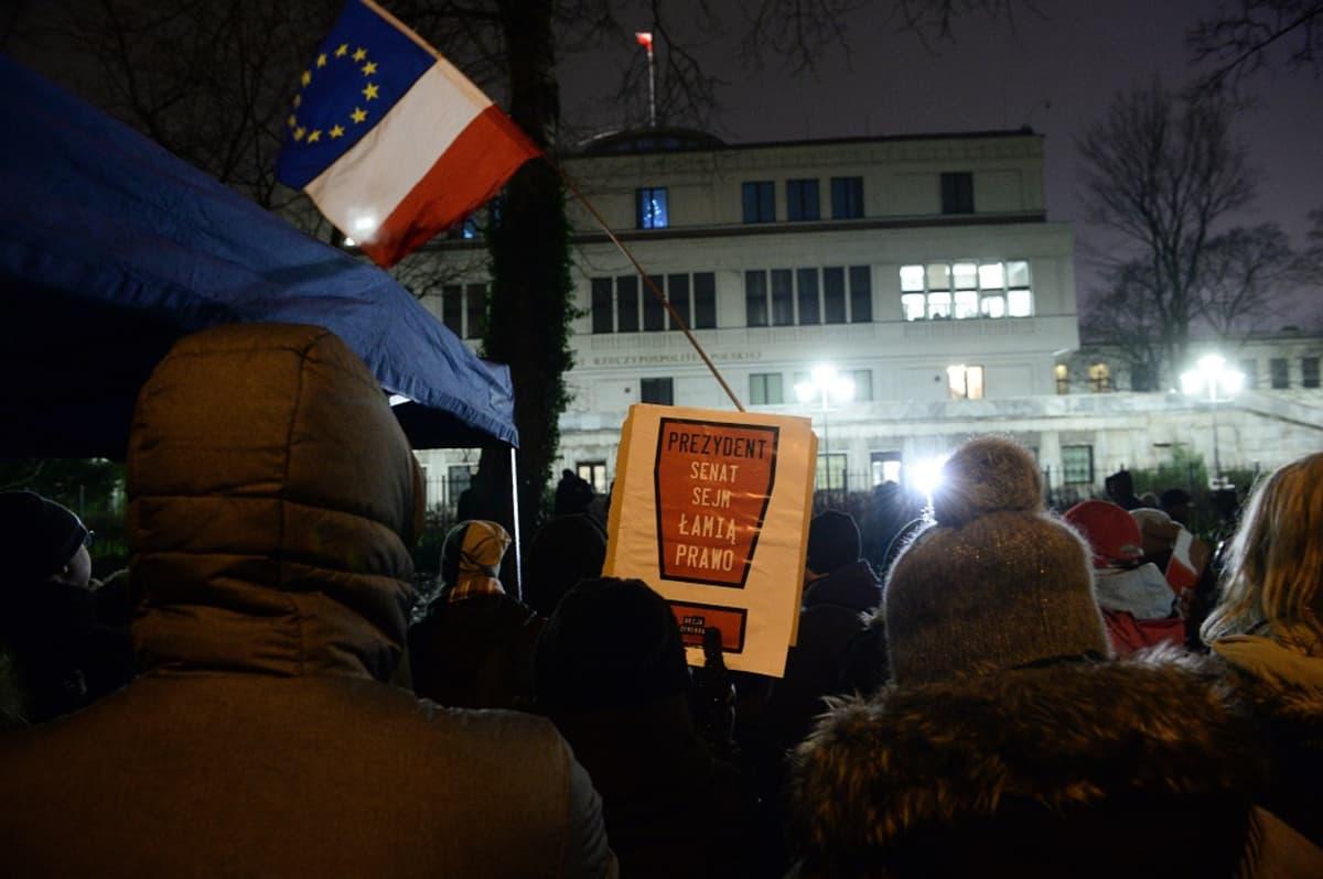 Väkijoukko seisoo vaalean rakennuksen edessä pimenevässä illassa. Joku pitää korkealla yhdistelmää EU:n ja Puolan lipuista.