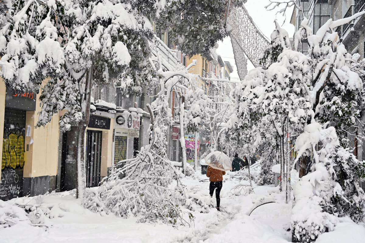 Ihmiset kahlaavat lumihangessa kaupungin kadulla.