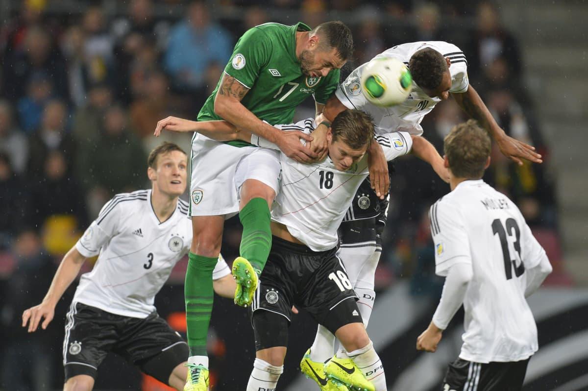Irlannin Damien Delaney taistelee pääpallosta yhdessä Saksan Toni Kroosin ja Jerome Boatengin kanssa.