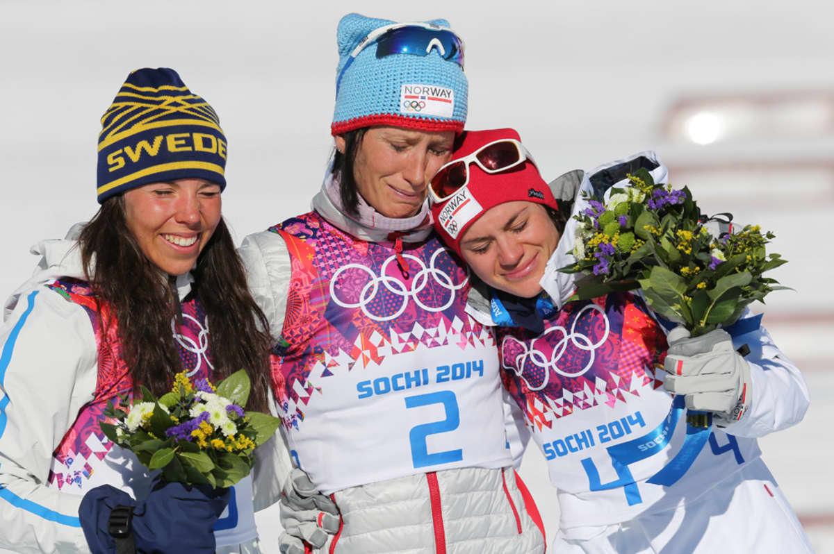 Sotshin naisten yhdistelmähiihdon mitalikolmikko Marit Björgen (kesk.), Charlotte Kalla (vas.) ja Heidi Weng (oik.) kukitusseremoniassa.