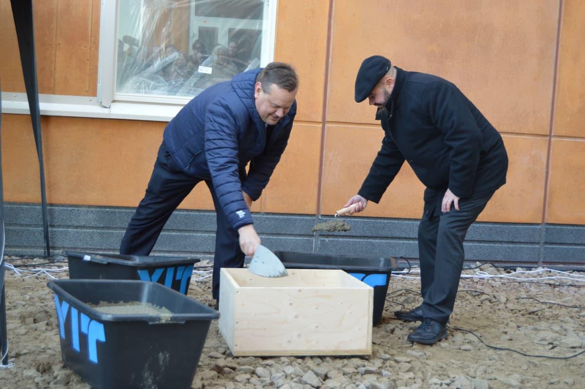 Kaksi miestä laittaa laastia puulaatikkoon.