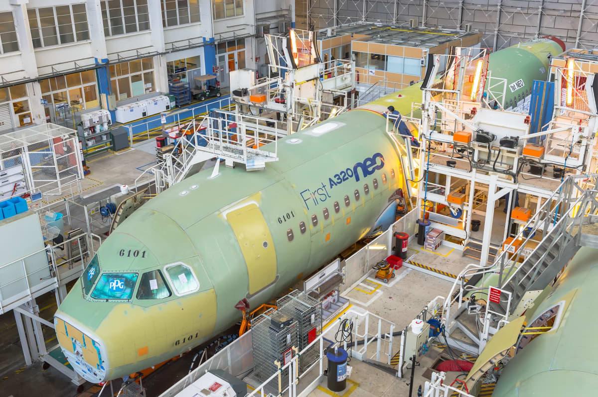 Lentokoneen runko hallin sisällä, ympärillä telineitä.
