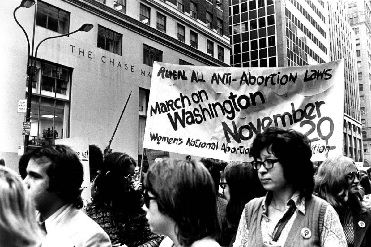 Mustavalkoisessa kuvassa nuoria naisia ja miehiä marssii aborttioikeutta vaativan banderollin kanssa.