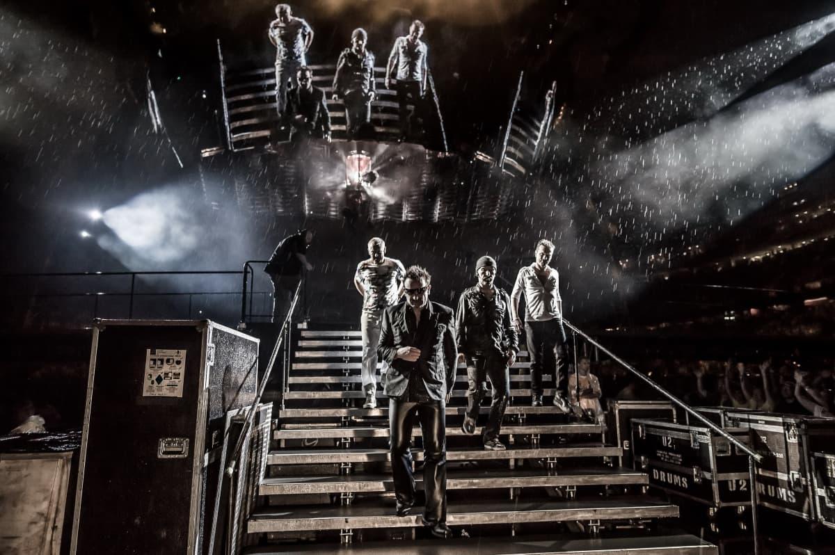 U2-bändi astelee alas 360-kiertueen lavalta rankassa vesisateessa Minneapoliksessa heinäkuussa 2011.