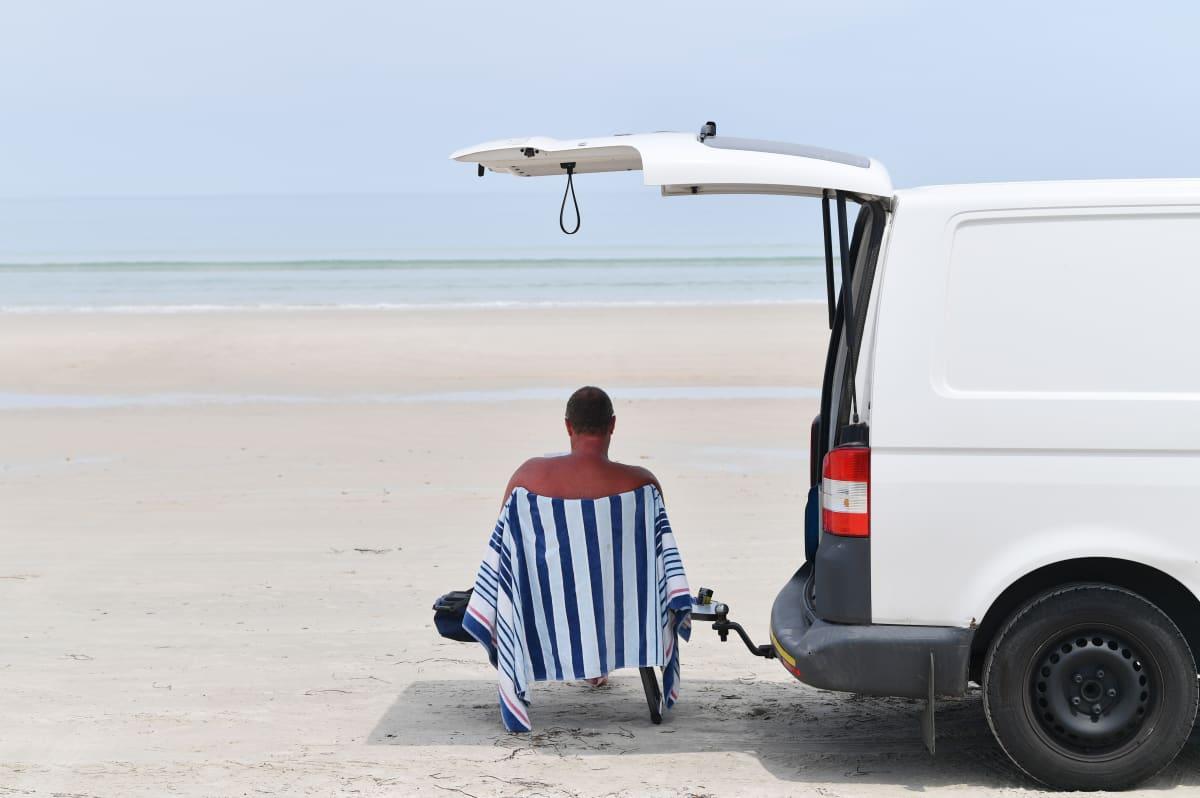 Mies istuu rannalla Adelaidessa Australiassa.
