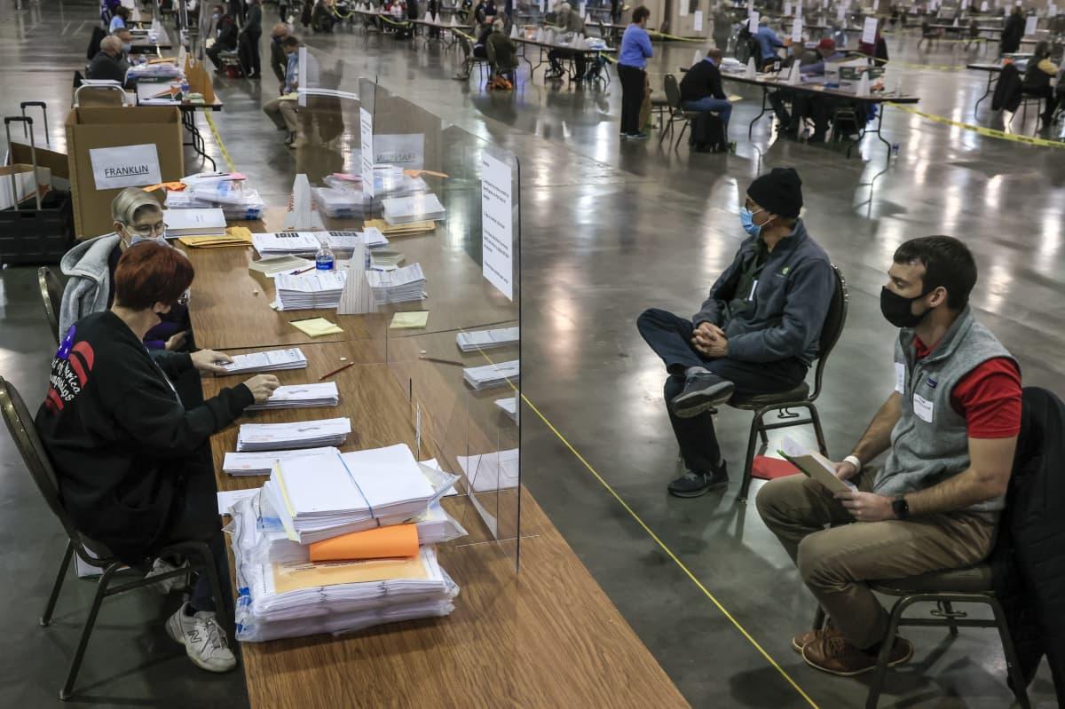 Vaalitarkkailijat (oikealla) seurasivat äänten uudelleenlaskentaa Milwaukeessa, Wisconsinissa 21. marraskuuta.