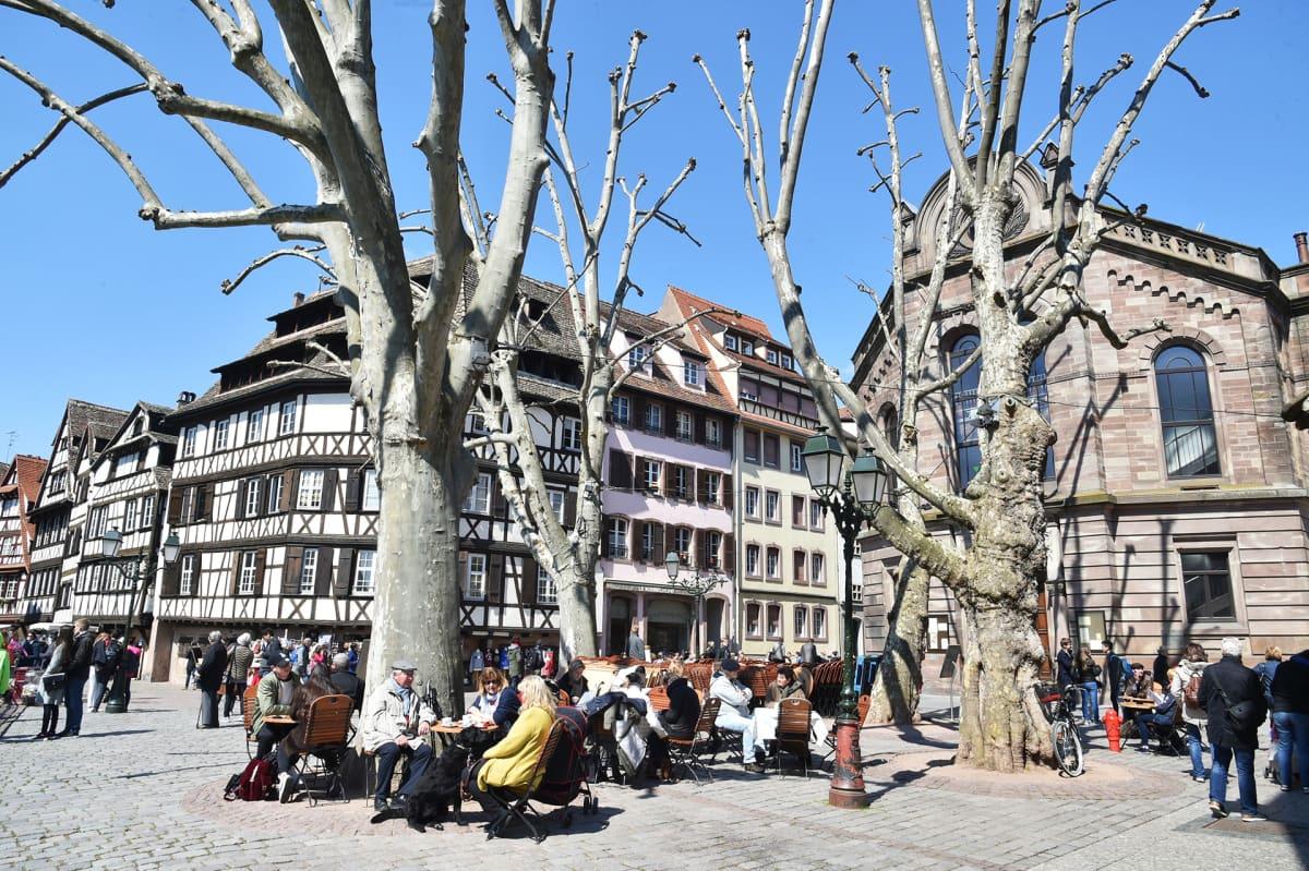 Ihmisiä kadulla ja katukahviloissa keväisessä Strasbourgissa.