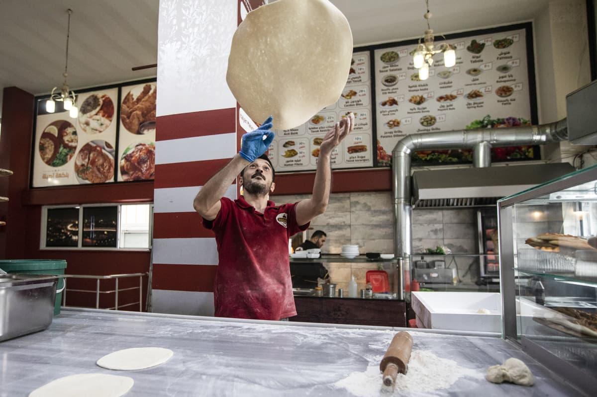 Mies heittä pizzapohjaa ilmassa.