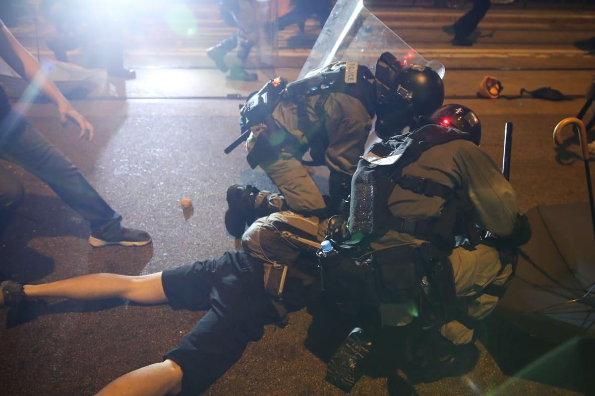 Poliisit painavat maahan mielenosoittajaa.