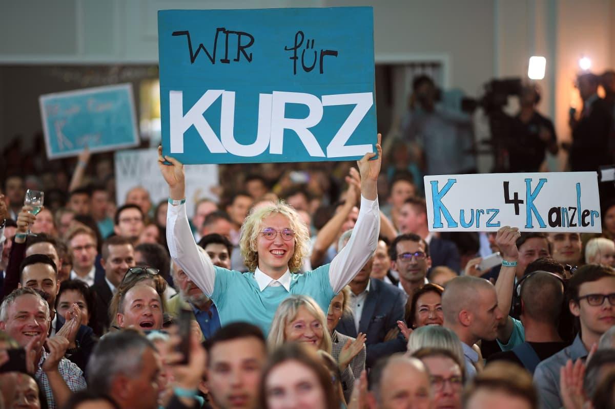 Ihmiset pitävät kylttejä, joissa osoitetaan tukea Sebastian Kurzille.