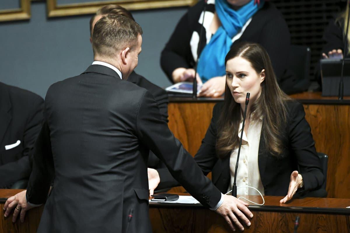Pääministeri Sanna Marin keskustelee Kokoomuksen puheenjohtajan Petteri Orpon kanssa eduskunnan täysistunnossa.